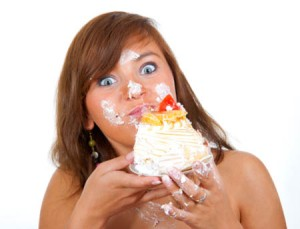 Girl eating cake with his hands, her face stained cream.